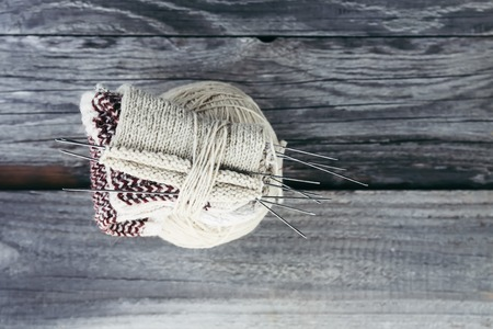 Ball of woolen yarn and knitting needles in a box on wooden boards background.