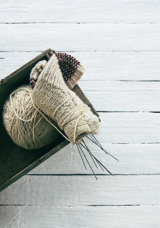Ball of rough woolen yarn and knitting needles in a box on white wooden boards background.