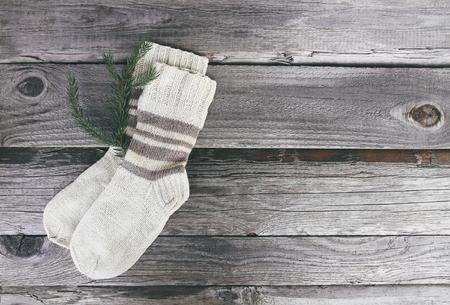 Handgemachte warme Stricksocken aus Wollgarn auf rauem Holzhintergrund. Standard-Bild