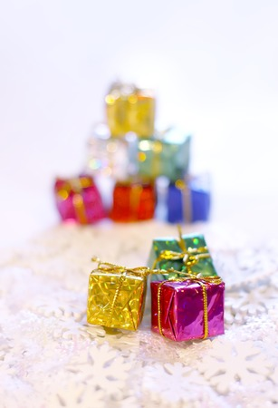 Group of small bright colorful gift boxes on white artificial snowflakes