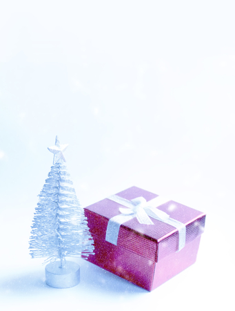 Decorative Christmas tree and gift box on fluffy snow Standard-Bild