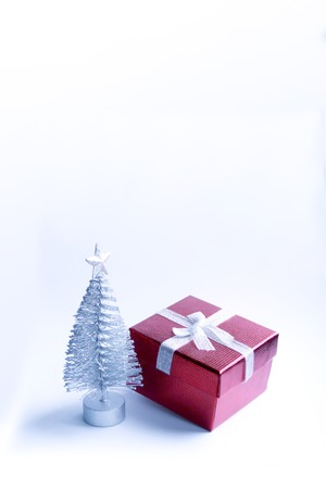 Decorative Christmas tree and red gift box on fluffy snow Standard-Bild