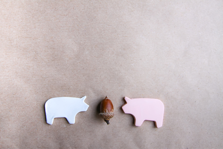 Two handmade clay pigs with acorn on craft paper