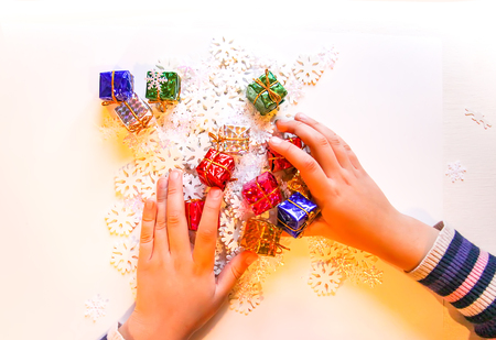 Small paper snowflakes and bright colorful gift boxes in childs hands. Cristmas and New Year gift decoration process.