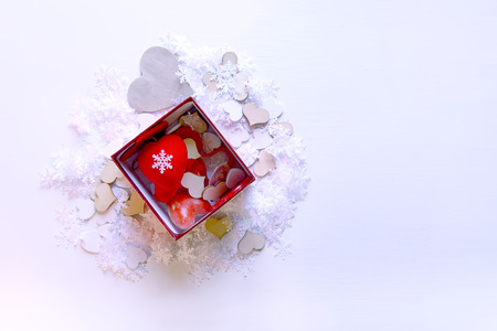 Artificial snowflakes and red decorative hearts in a box on white soft background. New Year and Christmas decor.