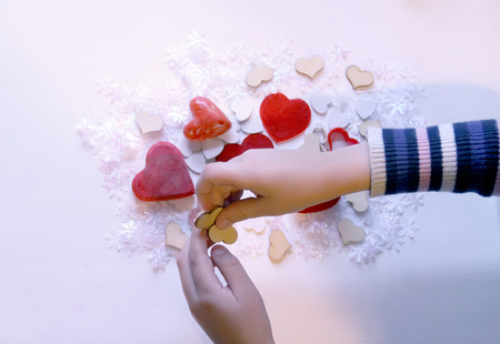 Small colorful hearts in child's hands. Gift decoration process.