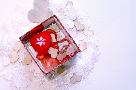 Artificial snowflakes and red decorative hearts in red gift box on white soft background. New Year and Christmas decor. Stock Photo