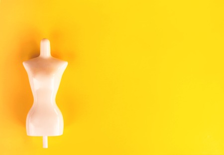 White plastic female mannequin figure on bright yellow background.