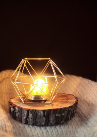 Warm light of hand made natural bee wax dying candle in a candleholder on wooden slice. Stok Fotoğraf