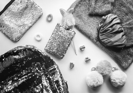Composition of fashion accessories and dress. Glitter sequins sweetshot, purse, backpack, pompons and hair bands. Different objects on soft background. Flat lay, top view. Black and white vintage style.
