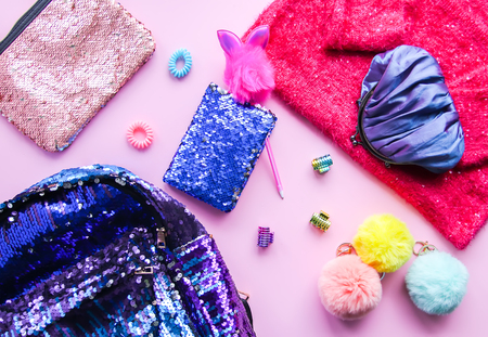 Bright composition of fashion accessories and dress. Glitter sequins sweetshot, purse, backpack, colorful pompons and hair bands. Different objects on soft pink pastel background. Flat lay, top view. Stock Photo