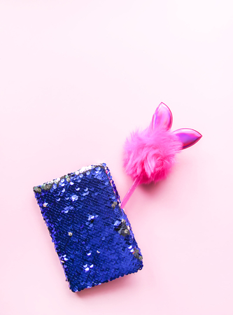 Bright composition of fashion accessories. Glitter sequins notepad and funny decorated pen. Objects on soft pastel background. Flat lay, top view.