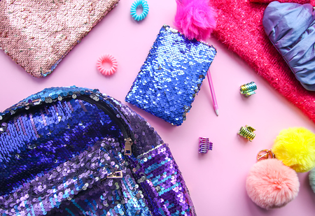Bright composition of fashion accessories and dress. Glitter sequins sweetshot, purse, backpack, colorful pompons and hair bands. Different objects on soft pink pastel background. Flat lay, top view. Foto de archivo