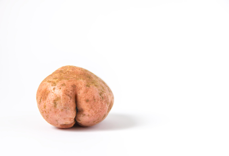 Raw funny potato in a shape of ass on white background.