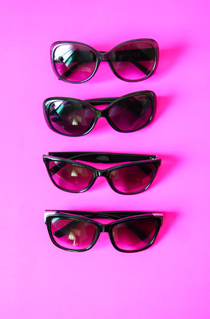Sunglasses on pink pastel background. Glasses with black frames. Eye UV protection fashion accessories.