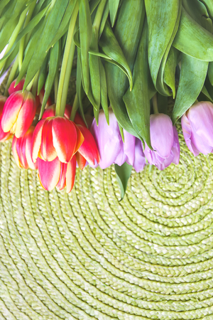Spring beautiful tulip flowers on green wicker place mat background. Mothers day, greeting card festive decorative floral composition. 版權商用圖片