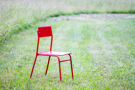 Red chair on green meadow om green grass