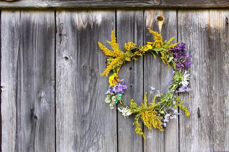 Wreath of wild flowers on the old wooden door