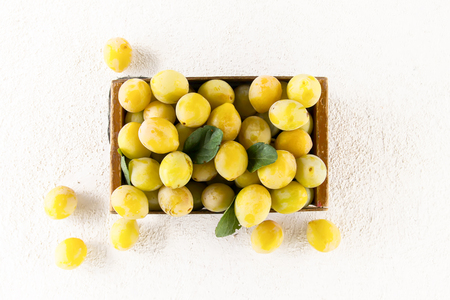 Fresh yellow plums. Ripe fruits in a wooden box on white background