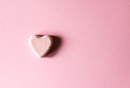 Pink small bath bomb in the shape of heart on soft pastel background Stock Photo