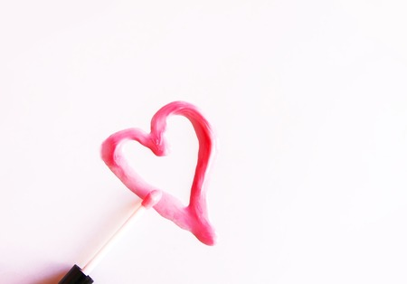 Heart drawn sample of pink lip gloss on a white background.