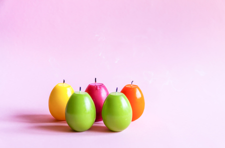 Traditional Easter decor. Group of bright paraffin candles in the shape of colorful eggs on soft pink background.