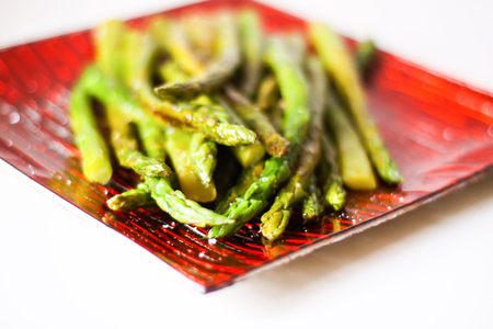 Green grilled asparagus on a red square glass plate 免版税图像