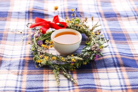 Summer composition with wreath of wildflowers and tea cup on a checkered plaid 写真素材