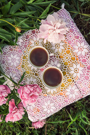 Tea in country style in summer garden in the village. Two cups of hot black tea on crocheted vintage lacy tablecloth and blooming peony flowers in sunlight.
