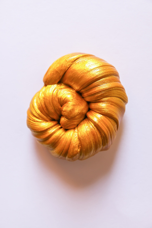 Golden plasticine soft stretchable texture. Anti-stress toy for kids activities, handmade, fun.