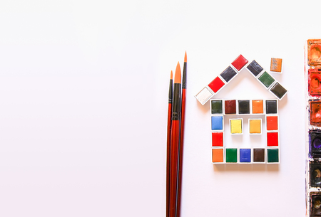 Watercolor paints in the shape of a funny house, brushes and paper on white background. Painting tools. Flat lay, top view
