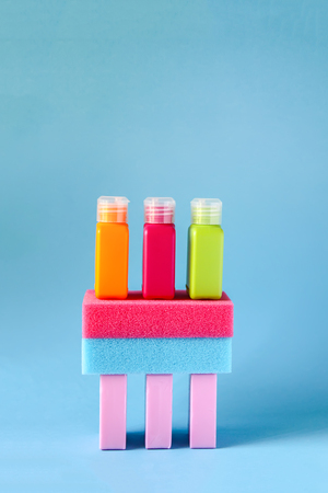 Colorful washcloths, plastic small travel bottles for liquids and bars of soap on a soft blue background. Accessories set for body care and hygiene.