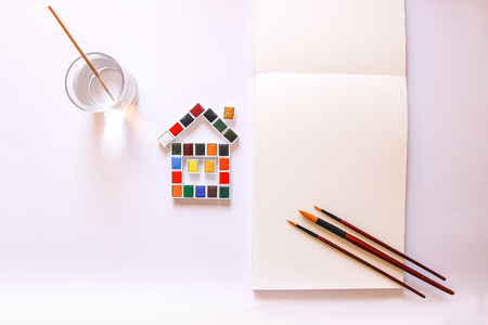Watercolor paints in the shape of a funny house, water in glass, brushes and paper on white background. Painting tools. Flat lay, top view