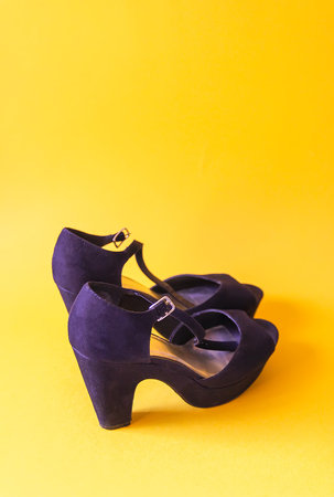Stylish black velvet shoes with high heels on bright yellow background Stok Fotoğraf