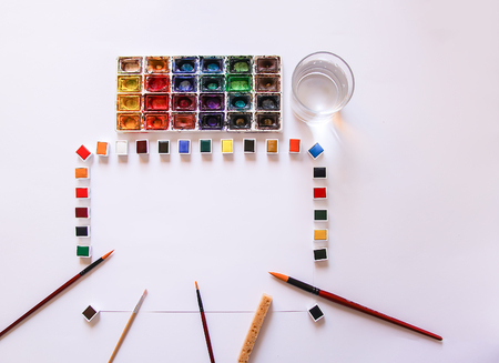Watercolor paints, water in glass, brushes and paper on white background. Painting tools. Flat lay, top view Stok Fotoğraf