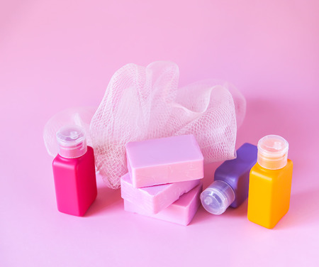 Colorful washcloth, plastic small travel bottles and bars of soap on a soft pink background. Accessories set for body care and hygiene.