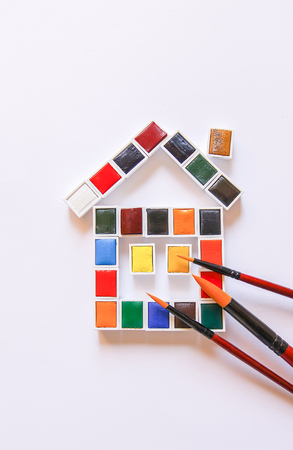 Watercolor paints in the shape of a funny house and paintbrushes on white background. Painting tools. Flat lay, top view.