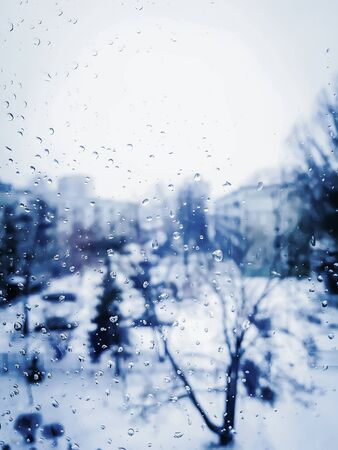 Misted window glass in winter day. Blurred nature background.
