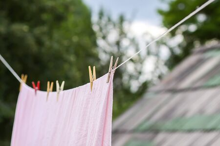 Freshly washed bed linen hanging on the rope outdoors. Clothes drying in rural yard.