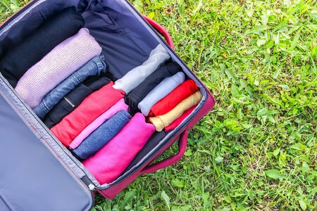 Open suitcase on the green grass with different clothes folded vertically. Vertical storage for easy and compact space saving in travel pack