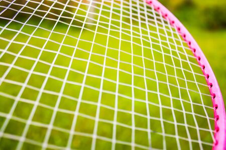 Badminton racket on green summer grass background close up.