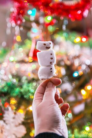 Funny marshmallow snowman on decorated Christmas tree blurred background 写真素材