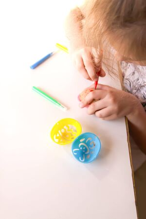 Child decorate Easter eggs with colored markers and plastic templates Banque d'images - 133784357
