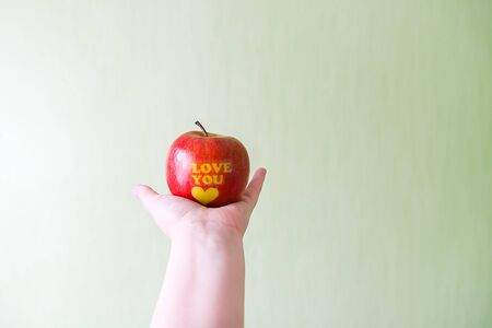 Fresh red apple in hand with words I love you and heart.