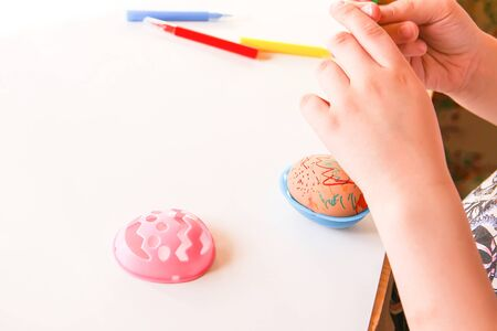 Child decorate Easter eggs with colored markers and plastic templates Banque d'images - 133784442