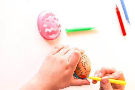 Child decorate Easter eggs with colored markers and plastic templates Banque d'images - 133784445