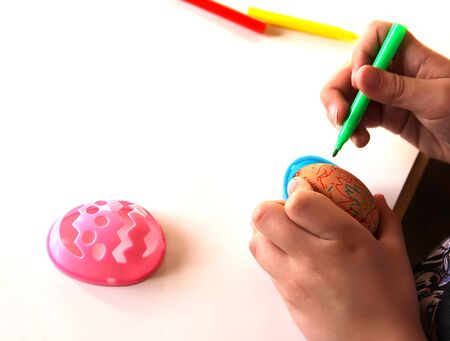 Child decorate Easter eggs with colored markers and plastic templates Banque d'images - 133784447
