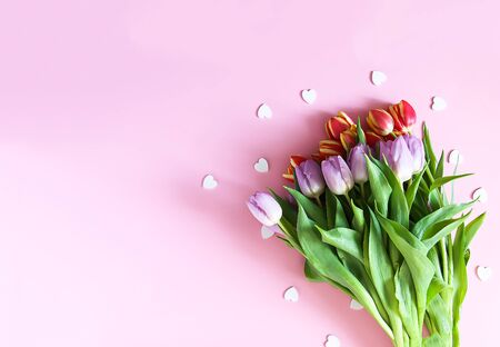 Womens day composition. Tulip flowers and small hearts on soft pink background.