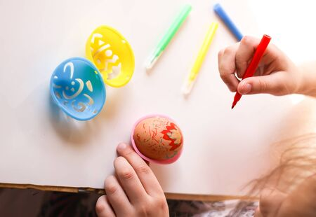Child decorate Easter eggs with colored markers and plastic templates