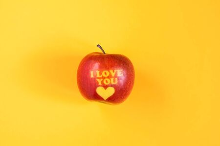 Fresh red apple with words I love you and heart on bright yellow background.